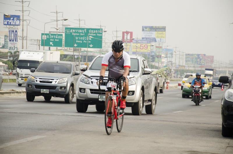 Bicicleta biking asiática de la gente tailandesa en raza en la carretera de la calle con el camino del tráfico fotografía de archivo libre de regalías