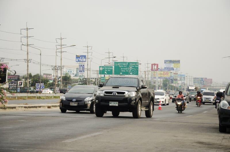 Bicicleta biking asiática de la gente tailandesa en raza en la carretera de la calle con el camino del tráfico fotografía de archivo