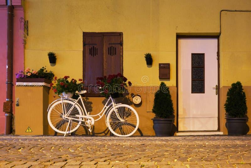 Bicicleta blanca decorativa con cestas de la flor en ella, un reloj en la pared cerca, una puerta blanca bloqueada, y una ventana fotografía de archivo libre de regalías