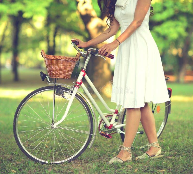 Bicicleta bonita da equitação da mulher no parque e em apreciar o dia ensolarado bonito imagem de stock