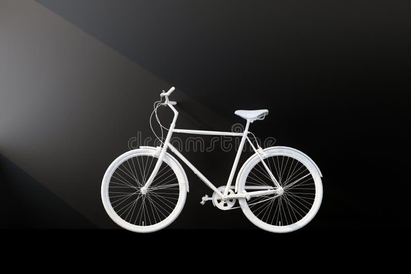 Bicicleta branca com parede preta fotografia de stock royalty free