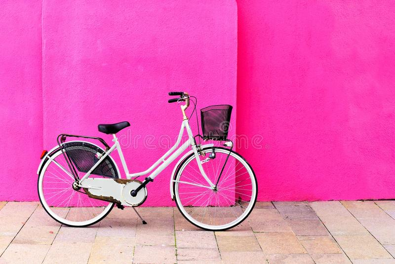 Bicicleta branca do vintage contra uma parede cor-de-rosa vibrante fotos de stock