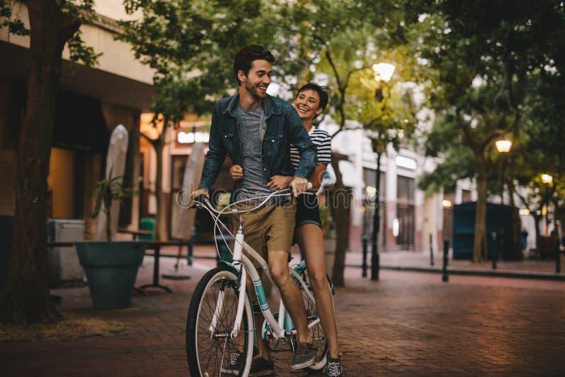 Bicicleta cariñosa del montar a caballo de los pares en el camino de ciudad fotografía de archivo
