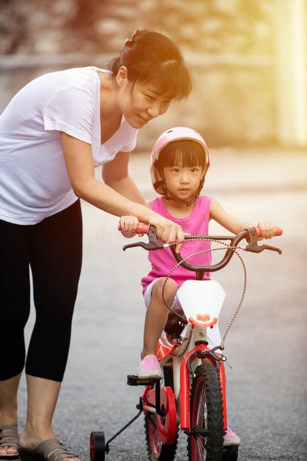 Bicicleta china asiática del montar a caballo de la niña con la guía de la mamá fotos de archivo