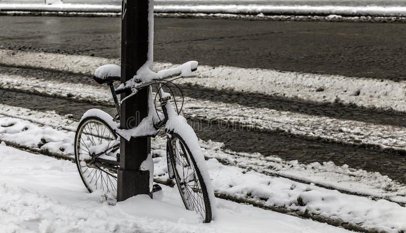 Bicicleta coberta com a neve em uma rua imagem de stock royalty free