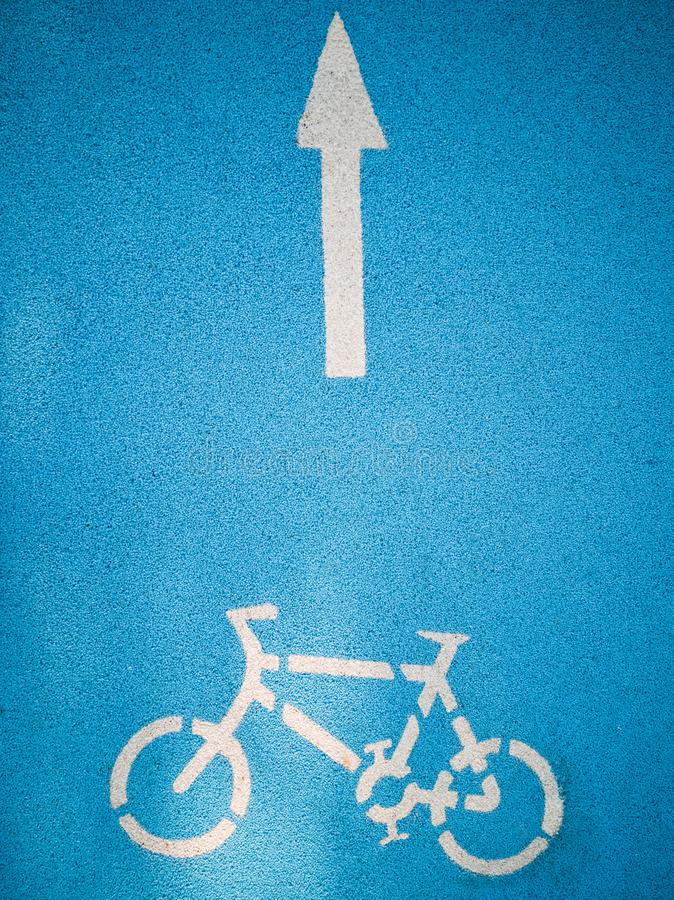 Bicicleta com os gráficos da seta na estrada azul fotografia de stock royalty free