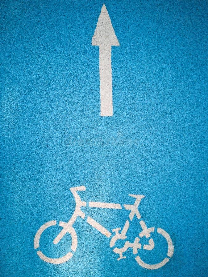 Bicicleta con los gráficos de la flecha en el camino azul fotografía de archivo libre de regalías