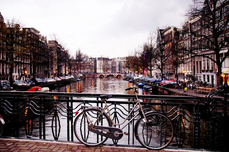 Bicicleta contra uma ponte pelo anoitecer, Amsterdão fotografia de stock royalty free
