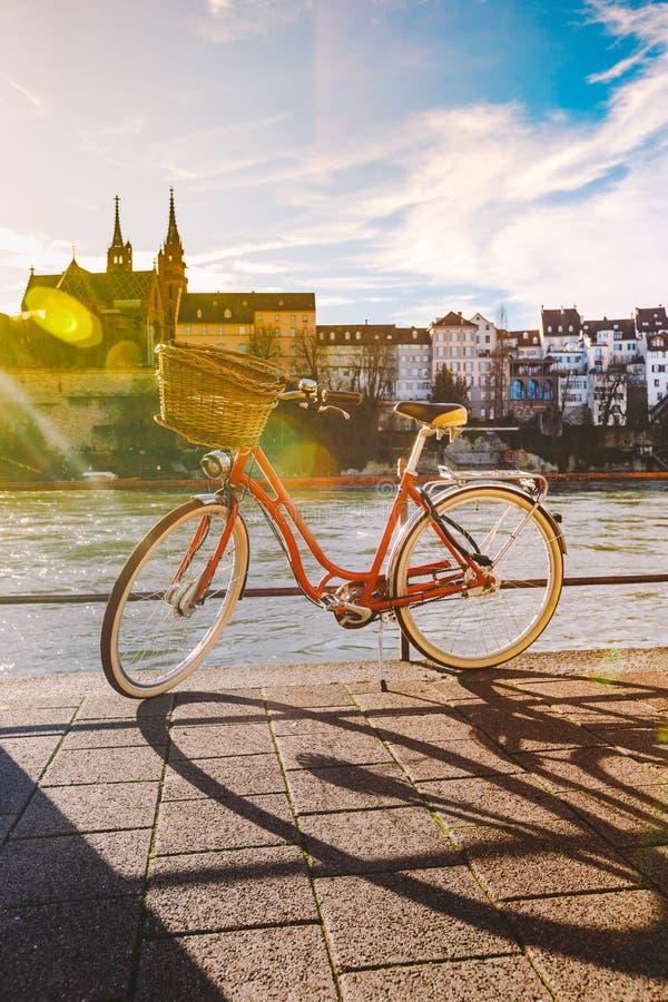 Bicicleta da cidade com a cesta no volante da cor vermelha no cais perto do Reno do rio em Suíça contra fotografia de stock