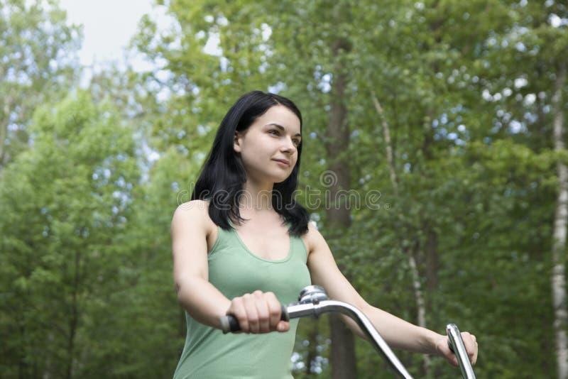 Bicicleta da equitação da mulher na floresta fotografia de stock royalty free