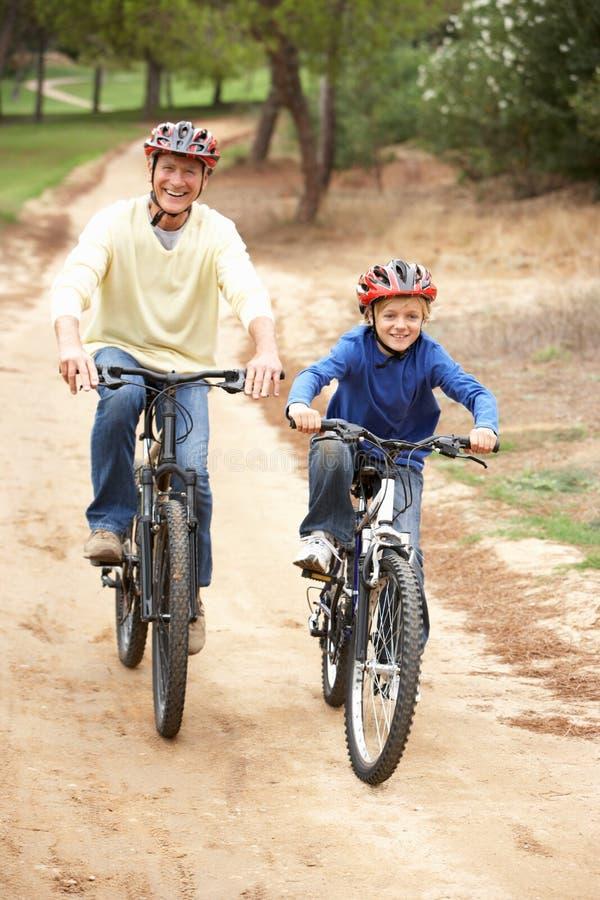 Bicicleta da equitação do avô e do neto no parque fotos de stock