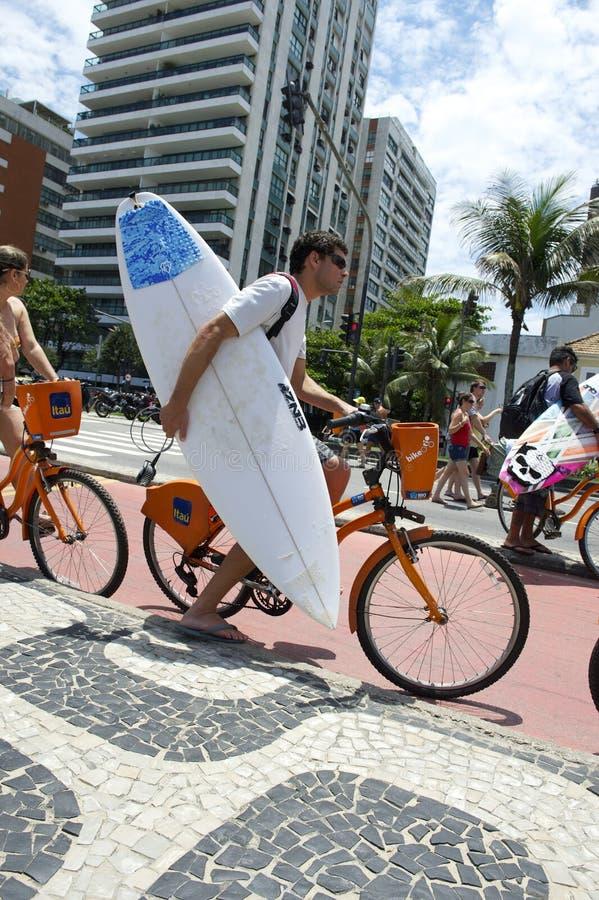 Bicicleta da equitação do homem com Rio da prancha fotografia de stock royalty free