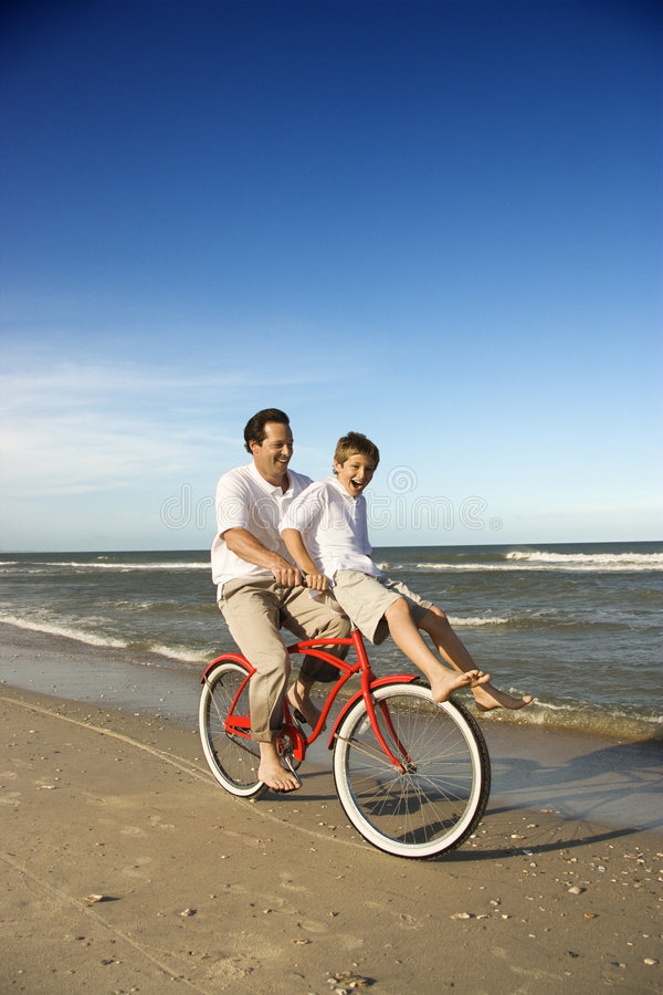 Bicicleta da equitação do paizinho e do filho imagem de stock