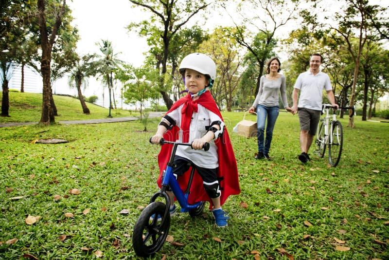 Bicicleta da equitação do rapaz pequeno do super-herói com a família no parque fotos de stock royalty free