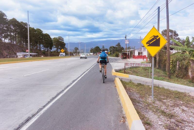 Bicicleta da equitação em uma estrada em Honduras centrais foto de stock