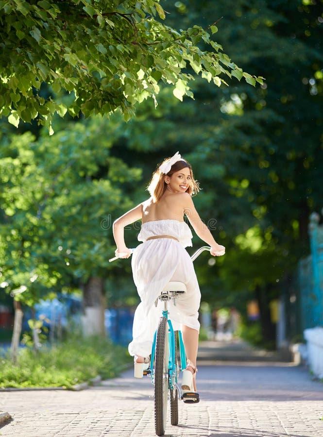 Bicicleta da equitação da jovem mulher nas ruas da cidade imagens de stock royalty free