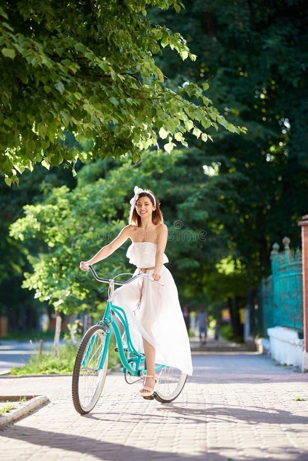 Bicicleta da equitação da jovem mulher nas ruas da cidade fotos de stock royalty free