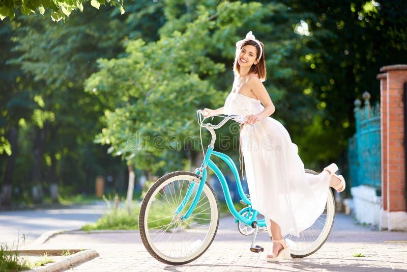 Bicicleta da equitação da jovem mulher nas ruas da cidade imagem de stock