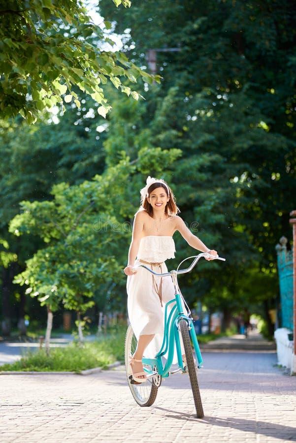 Bicicleta da equitação da jovem mulher nas ruas da cidade foto de stock royalty free