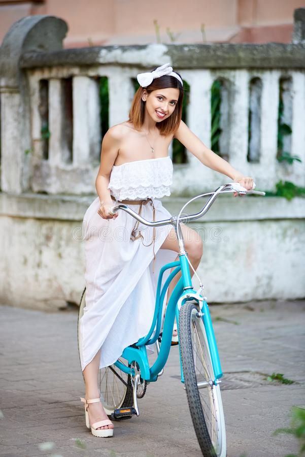 Bicicleta da equitação da jovem mulher nas ruas da cidade foto de stock