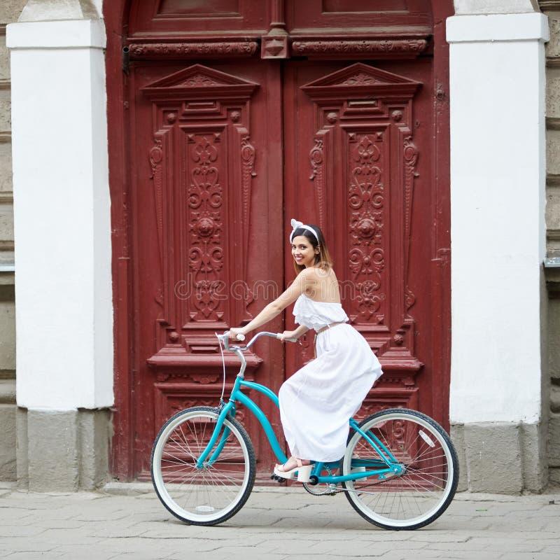 Bicicleta da equitação da jovem mulher nas ruas da cidade imagem de stock royalty free