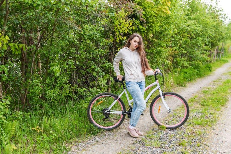 Bicicleta da equitação da jovem mulher no parque da cidade do verão fora Povos ativos A menina do moderno relaxam e a bicicleta d fotografia de stock
