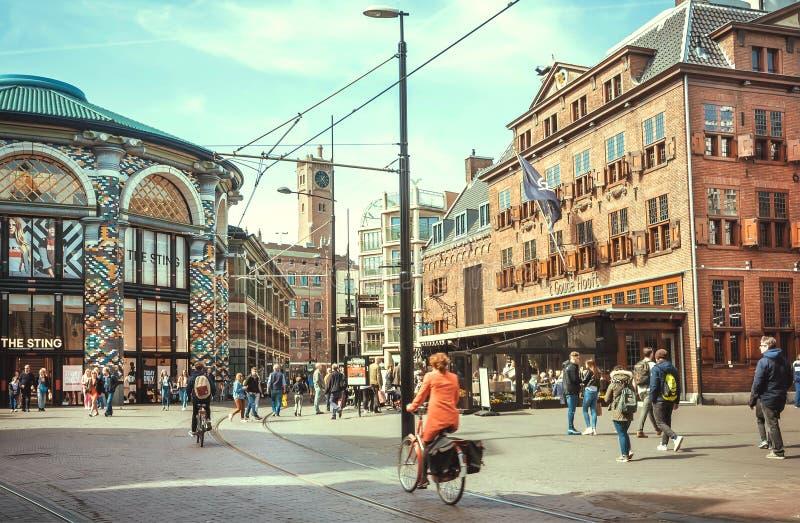 Bicicleta da equitação da mulher na rua com os shopping na cidade holandesa histórica imagem de stock royalty free