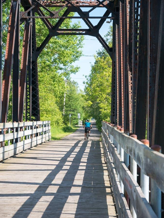 Bicicleta da equitação da mulher no campo Chicoutimi, Saguenay, Quebeque, Canadá fotos de stock royalty free