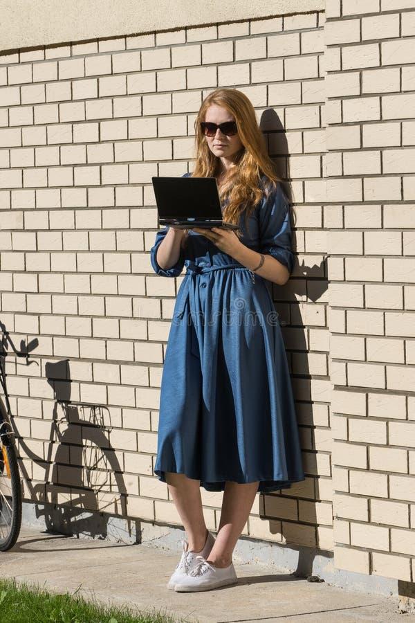 Bicicleta da mulher e do vintage e parede de tijolo branca, gramado verde A menina loura é ereta fora de um escritório, terra arr fotos de stock