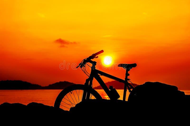 Bicicleta da silhueta com por do sol do mar no crepúsculo imagem de stock