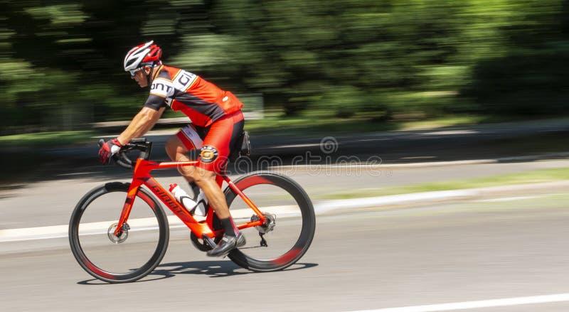 Bicicleta das corridas de automóveis da equitação para baixo em Central Park fotos de stock