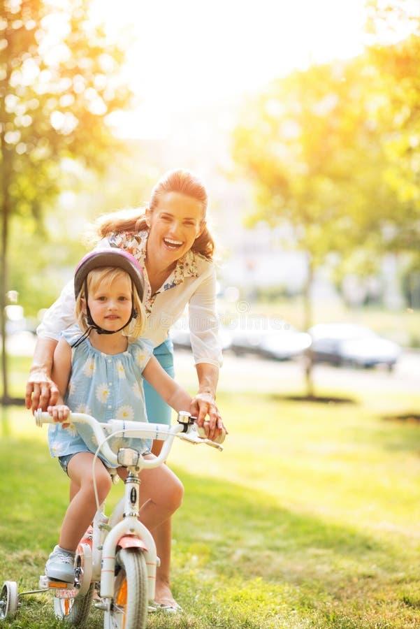 Bicicleta de ajuda da equitação do bebê da mãe no parque foto de stock royalty free