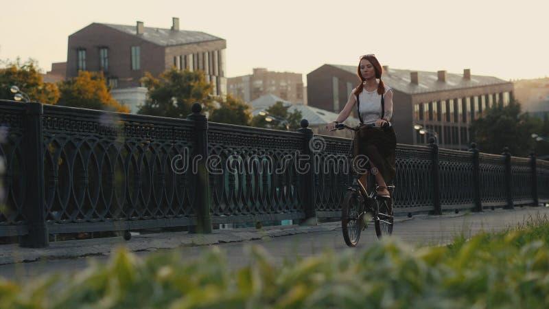 Bicicleta de cabelo vermelha da equitação da mulher na cidade na construção da fachada do fundo fotografia de stock