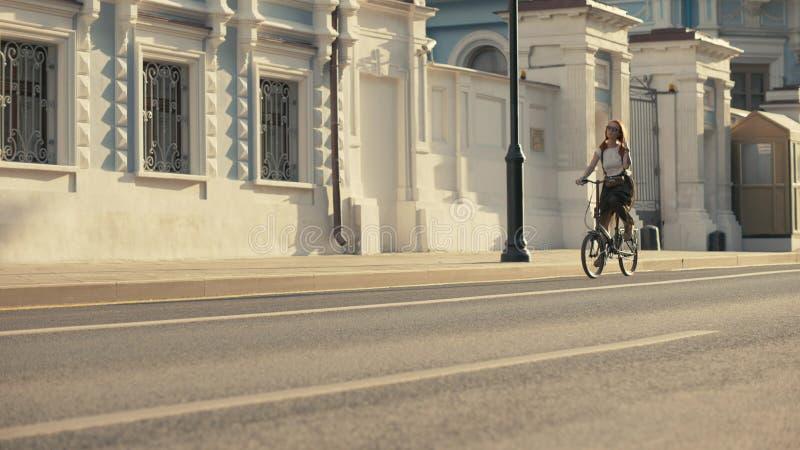 Bicicleta de cabelo vermelha da equitação da mulher na estrada de cidade na construção do fundo foto de stock royalty free