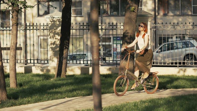 Bicicleta de cabelo vermelha da equitação da mulher no parque da cidade no dia ensolarado foto de stock royalty free