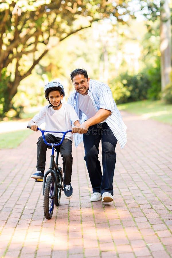 Bicicleta de enseñanza del hijo del padre fotos de archivo