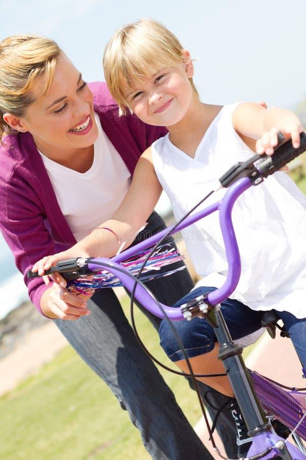 Bicicleta de enseñanza del paseo de la muchacha de la madre fotografía de archivo