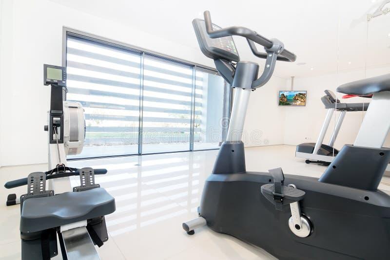 Bicicleta de exercício e simulador do enfileiramento em um gym luxe moderno. imagens de stock