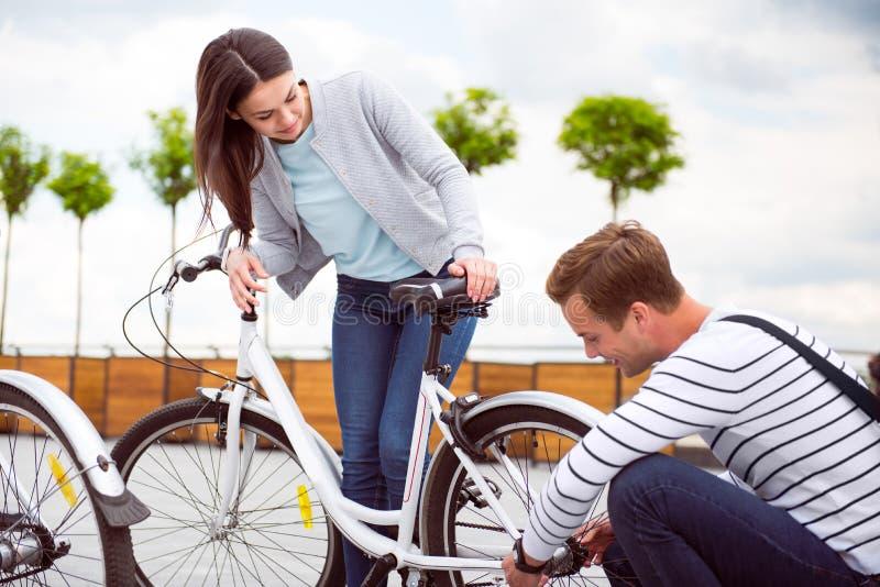 Bicicleta de la fijación del hombre joven de la muchacha imágenes de archivo libres de regalías