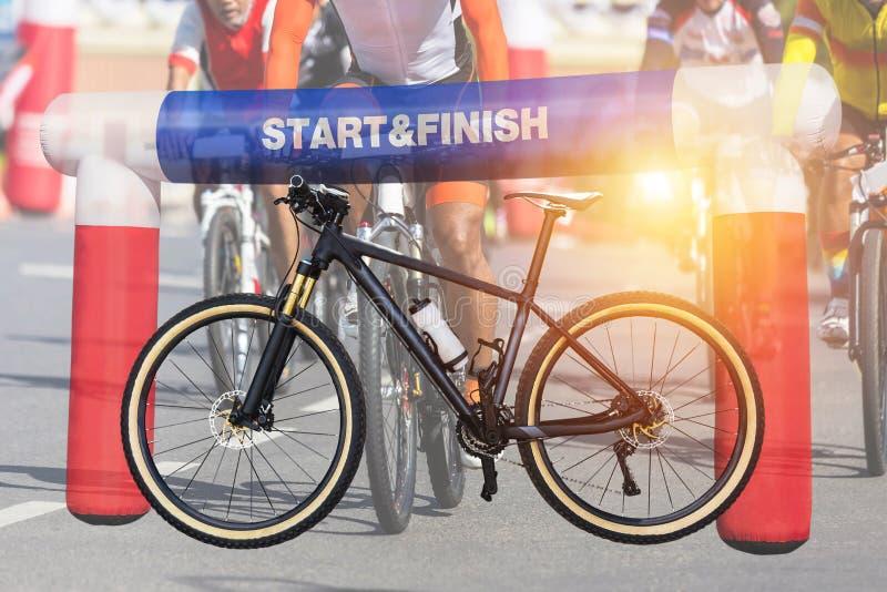 Bicicleta de la montaña de la exposición doble y comienzo inflable - acabe el arco con los ciclistas durante el deporte de la bic foto de archivo libre de regalías