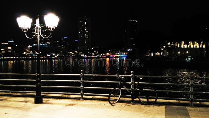 Bicicleta de la noche y lámpara de calle imagenes de archivo