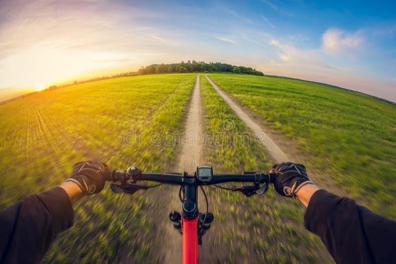 Bicicleta de montada na estrada de terra no campo no por do sol, vista de primeira pessoa, lente de fisheye da perspectiva da dis fotografia de stock