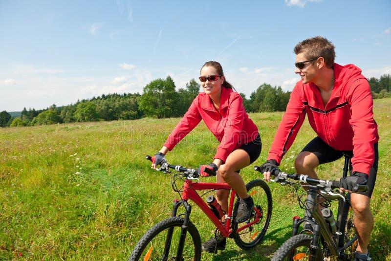Bicicleta de montanha Sportive da equitação dos pares no prado imagem de stock