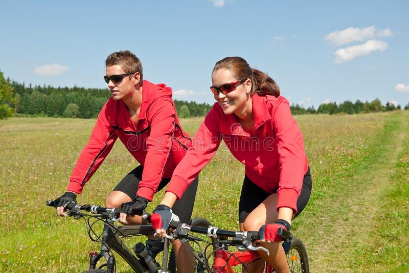 Bicicleta de montanha Sportive da equitação dos pares no prado fotografia de stock