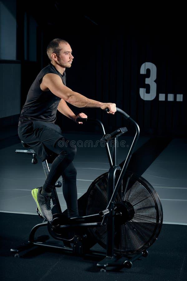 Bicicleta de utilização masculina do ar da aptidão para o cardio- exercício no gym funcional do treinamento foto de stock royalty free