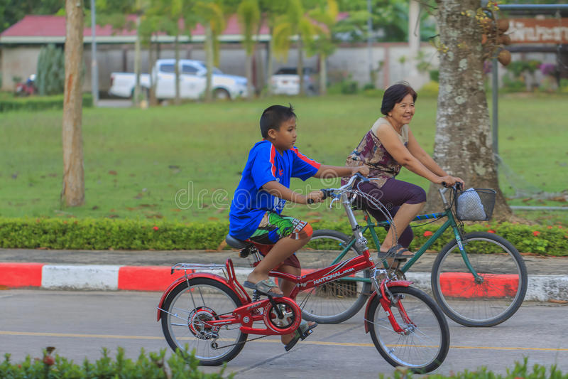 Bicicleta del montar a caballo de la abuela y del nieto en parque imagenes de archivo