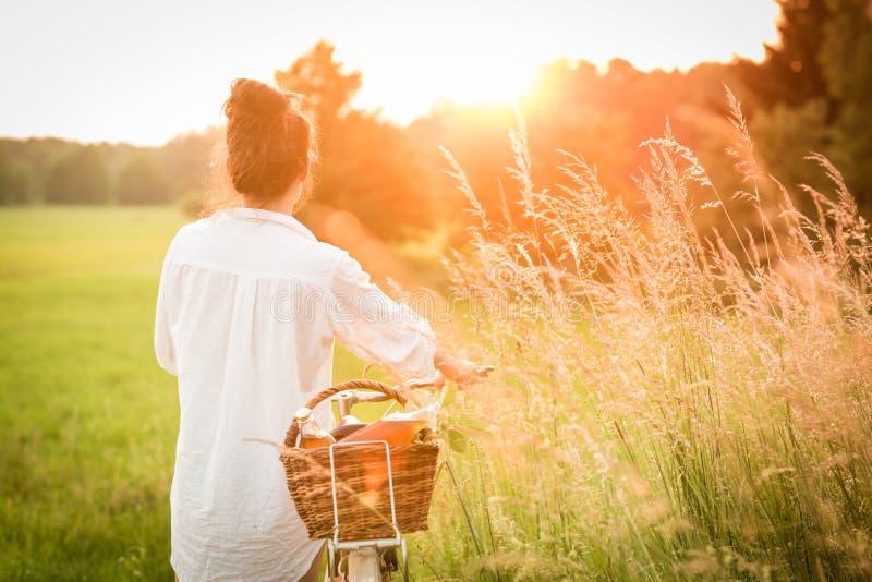 Bicicleta del montar a caballo de la mujer con la cesta de comida fresca imagenes de archivo