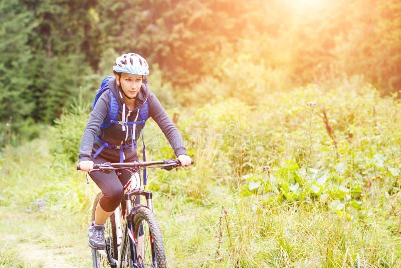 Bicicleta del montar a caballo de la mujer joven en bosque de la montaña imagenes de archivo