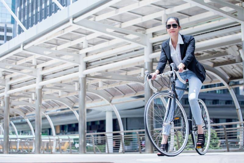 Bicicleta del montar a caballo de la mujer de negocios a trabajar en la calle en ciudad transporte y sano elegante fresco de la f imágenes de archivo libres de regalías