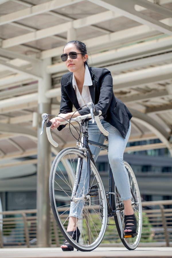 Bicicleta del montar a caballo de la mujer de negocios a trabajar en la calle urbana transporte y sano elegante fresco de la form imagen de archivo libre de regalías